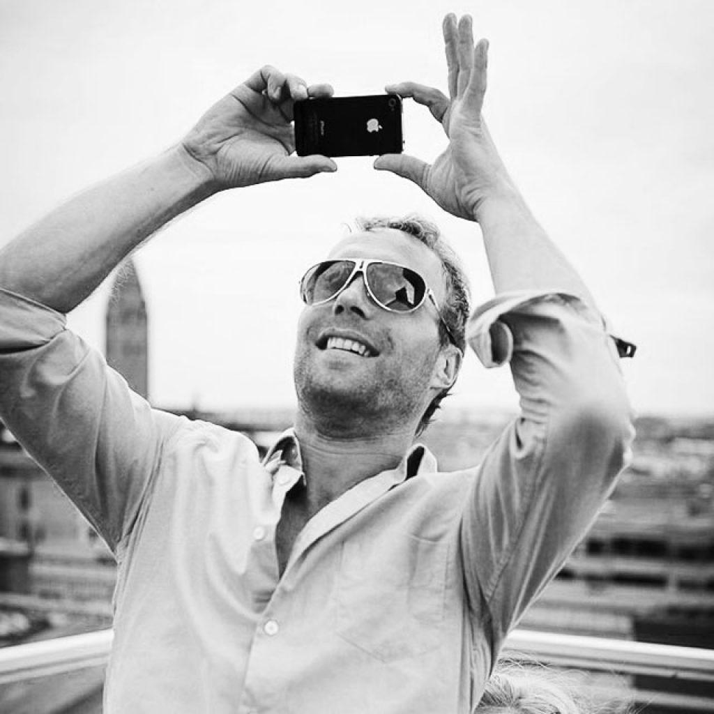 Porträtt på fotograf Peter Nilsson, fotograferar med iPhone
