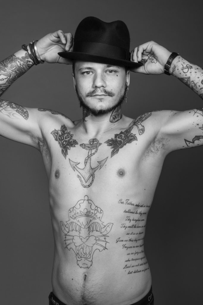 Tatuerare Fredrik Jr håller i hatt, svartvitt
