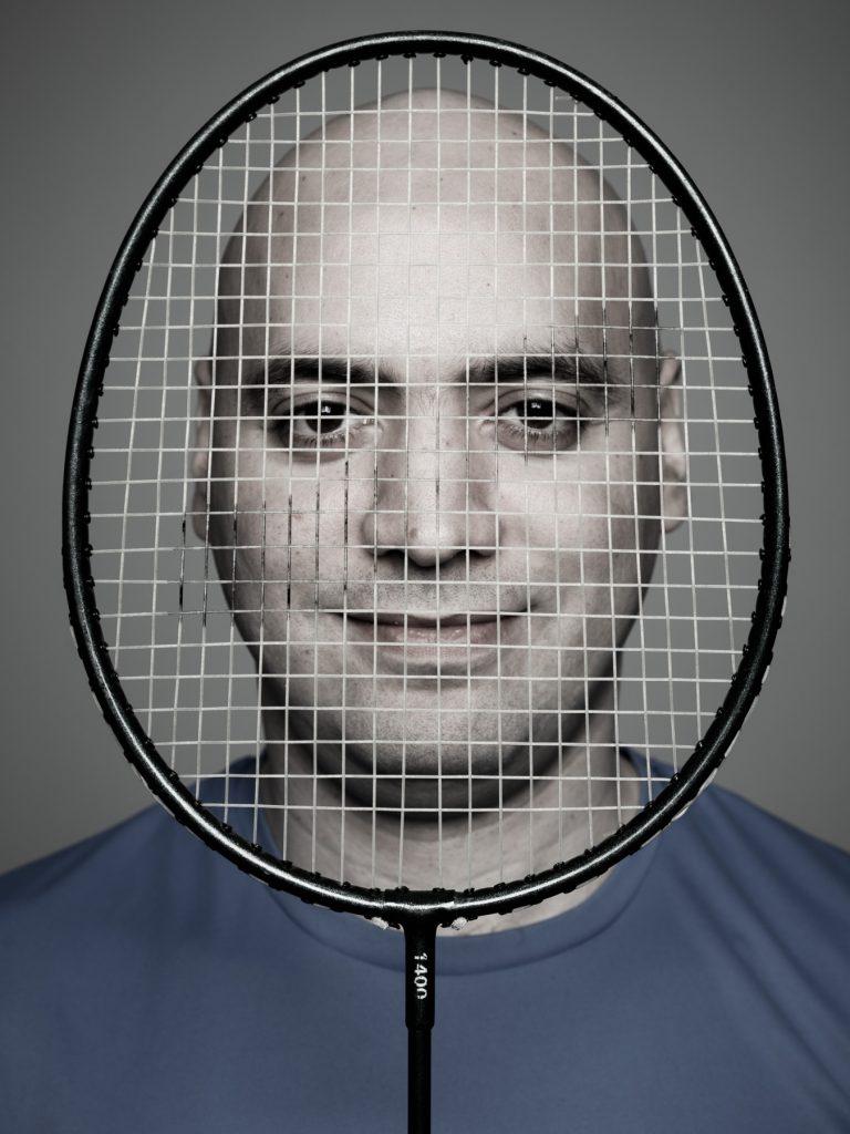 personalporträtt, man håller badmintonracket framför ansiktet