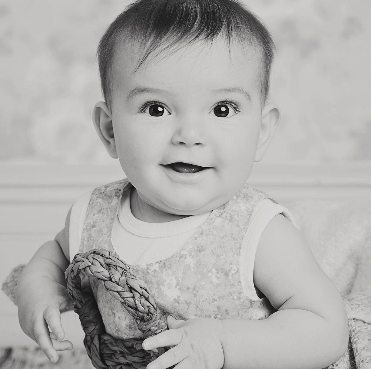 bebis sitter i korg i svartvitt